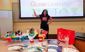 Braylee standing in front of a projector screen and giving a presentation on Gleim at an accounting club meeting at Colorado Mesa University