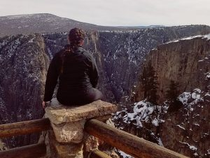 Braylee sitting on a hiking trail barrier that overlooks a canyon in Colorado.
