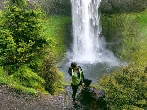 Braylee standing by a waterfall on a hiking trail in Oregon.