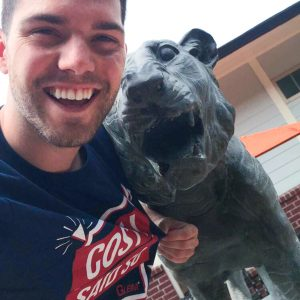 Austin, wearing his Gleim Campus Rep shirt, taking a selfie with a statue of LSU's mascot.