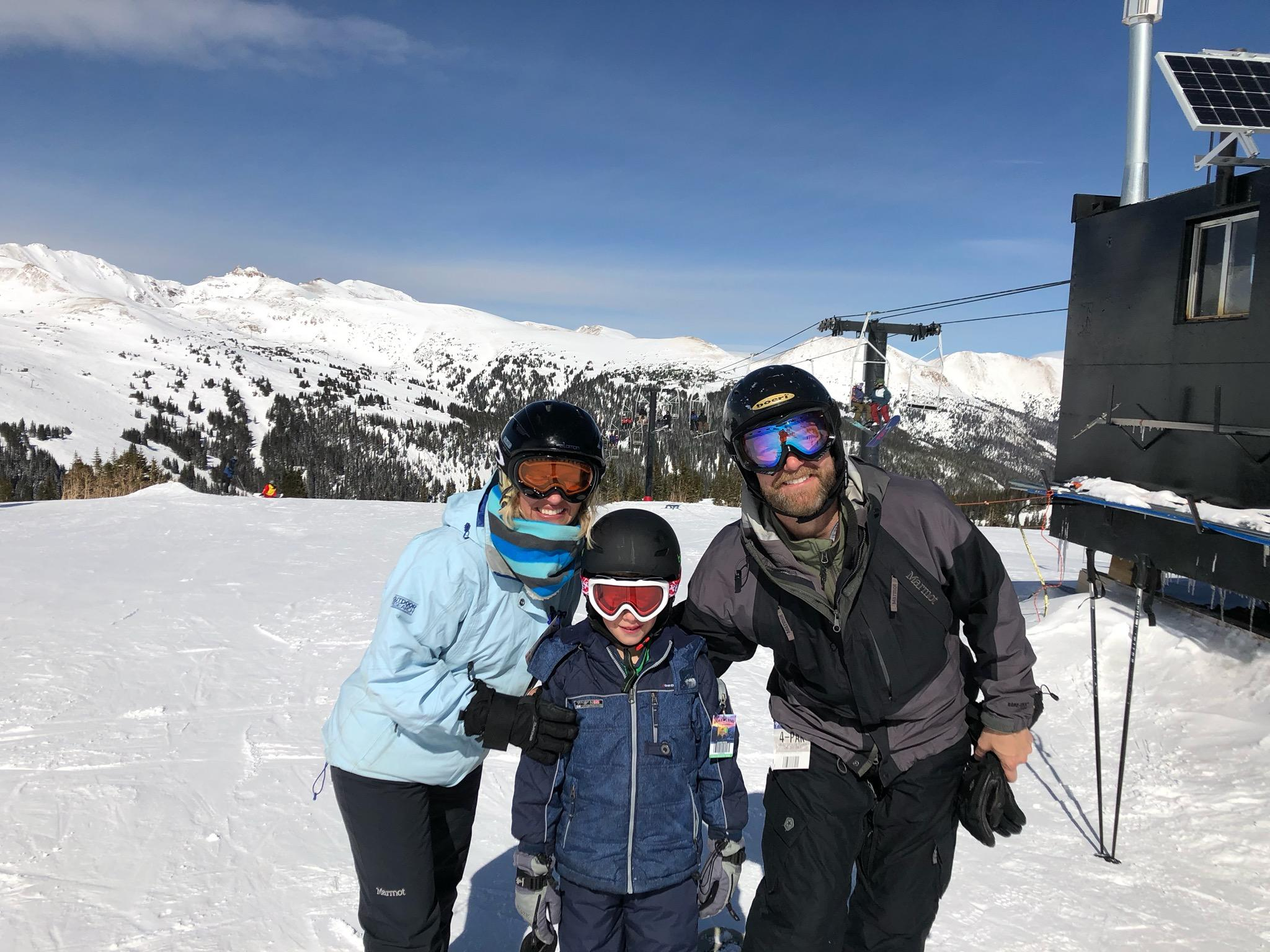 Casie Cook and her family standing on a snow covered mountain.